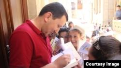 """""""Kitabsevərlər"""" qrupunun təşkilatçısı Fariz Bayramov uşaqlar üçün Astrid Lindqrenin kitabını imzalayır."""