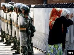 Две женщины-уйгурки смотрят сквозь полицейское ограждение. Урумчи, 9 июля 2009 года.