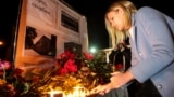 A young woman lights candles in the city of Simferopol, Crimea, in memory of the victims of the October 17 Kerch polytechnic school attack.
