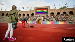 "Demonstrators raise rainbow flags at Stockholm's Olympic Stadium during a protest over a controversial Russian law banning gay ""propaganda."" Some athletes attending the upcoming Winter Olympics in Russia have also pledged to denounce the legislation even though explicit political statements are forbidden by the Olympic Charter."