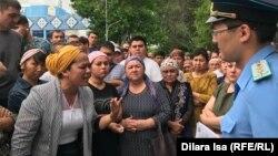 Былтыр пышақталып қайтыс болған Хусан Турдиевтің туысы Камала Турдиева (сол жақта) қалалық прокуратура алдында полицеймен сөйлесіп тұр. Шымкент, 21 мамыр 2019 жыл.