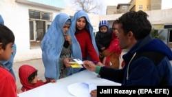 ارشیف، هرات کې یو بشردوستانه فعال یوې افغانې کورنۍ ته د بشري مرستو د ورکولو لپاره د نوم لیکنې پر مهال