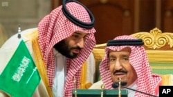 Saudi Crown Prince Mohammed bin Salman, left, speaks to his father, King Salman, right, at a meeting of the Gulf Cooperation Council in Riyadh, Saudi Arabia, Sunday, Dec. 9, 2018. Leaders of Gulf
