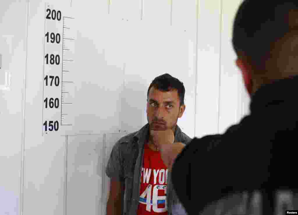 A migrant, who said he was from Afghanistan, is photographed by police after entering Serbia from Macedonia.