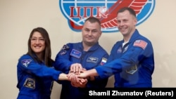U.S. astronauts Christina Koch and Nick Hague and Russia's Aleksei Ovchinin (center) pose before their launch.