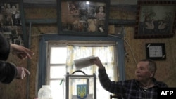An elderly man casts ballot from home in Orane, near Kyiv, on January 17.