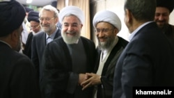 President Hassan Rouhani shaking hands with Amoli Larijani, with Ali Larijani on the left. Undated. File photo
