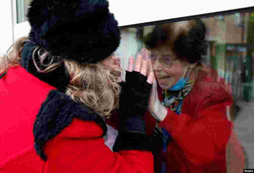 Жінка в карнавальному костюмі спілкується через вікно з жінкою, яка проживає у центрі довгострокового перебування для літніх людей