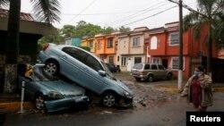 Žena sa zaštitnom maskom prolazi pored uništenih automobila u tropskoj oluji 'Amanda', San Salvador, El Salvador, 31 maj 2020.