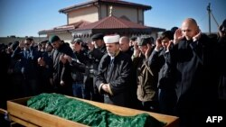 Members of the Crimean Tatar community pray over the coffin of Reshat Ametov during his funeral in Simferopol on March 18. His body bore the marks of a violent death, according to Human Rights Watch.