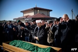 Members of the Crimean Tatar community pray over the coffin of Reshat Ametov during his funeral in Simferopol on March 18, 2014. He was found dead on the day of the referendum. His body bore signs of torture.