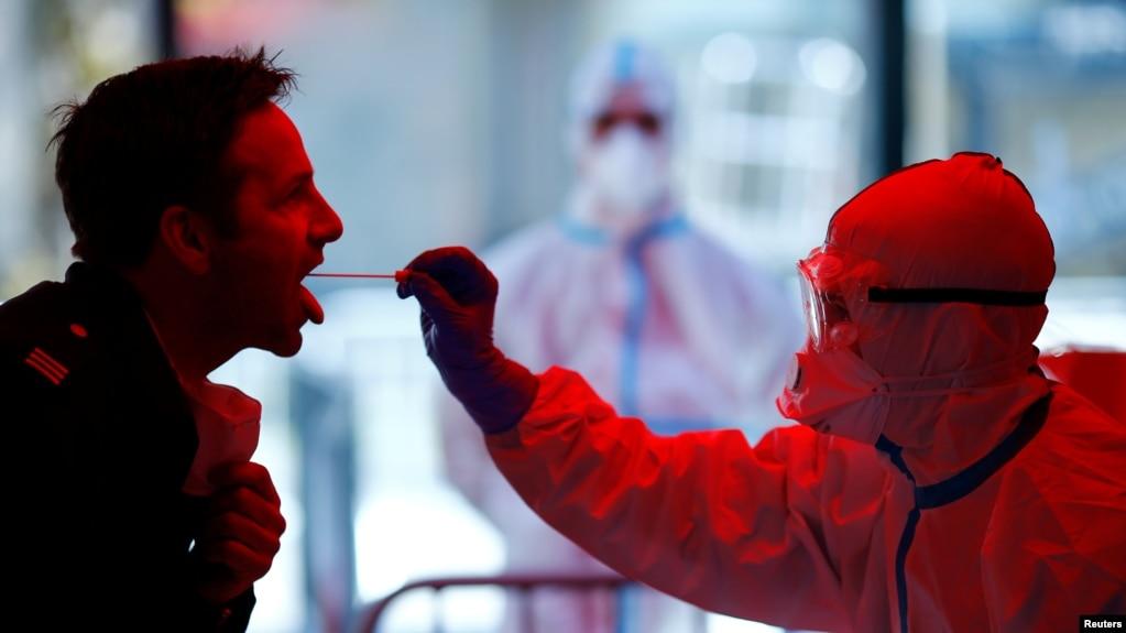 """Медицинский работник берёт у пациента тест на коронавирус в специальном пункте, где обслуживаются """"люди опасных профессий"""" – полицейские, медсестры, пожарные. Кёльн"""