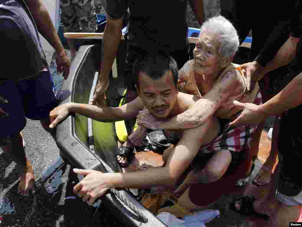A man carries an elderly woman during an evacuation from a flooded area of Thailand's Pathum Thani province, in Bangkok's suburbs. (Sukree Sukplang for Reuters)