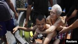 Бангкок маңындағы Патхумтхани губерниясында тасқын су басқан елді мекеннен жұртты көшіру кезінде қарт әйелді арқалаған адам. Таиланд, 21 қазан 2011 ж.