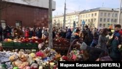 """Люди несут к сгоревшему ТРЦ """"Зимняя вишня"""" цветы и игрушки"""