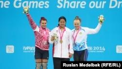 Казахстанская штангистка Татьяна Капустина (справа) со Светланой Щербаковой (слева) и Дуанганксорн Чайди. Нанкин, 22 августа 2014 года.