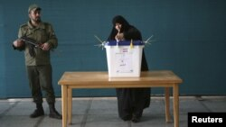 A woman from the Iranian city of Qom casts her vote in parliamentary elections on March 2 as a policeman stands guard.