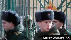 A Russian soldier guards the entrance to St. Petersburg's Mozhaisky Academy while students evacuate following a blast at the facility on April 2.