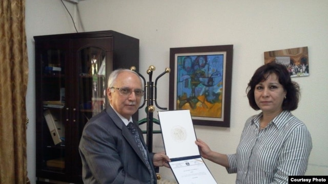 RFI correspondent Faiqa Rasul Srhan receives her certificate of merit from the cultural attaché for the Iraqi Embassy in Jordan.
