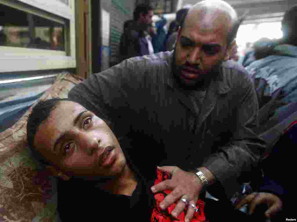 A protester attends to an injured man during clashes in Cairo on January 28.