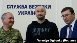 Arkady Babchenko (center) stands beside Ukrainian Prosecutor-General Yuriy Lutsenko (right) and the head of the state security service (SBU), Vasiliy Gritsak, during a news briefing in Kyiv where it was revealed that Babchenko's supposed killing was part of a sting operation.