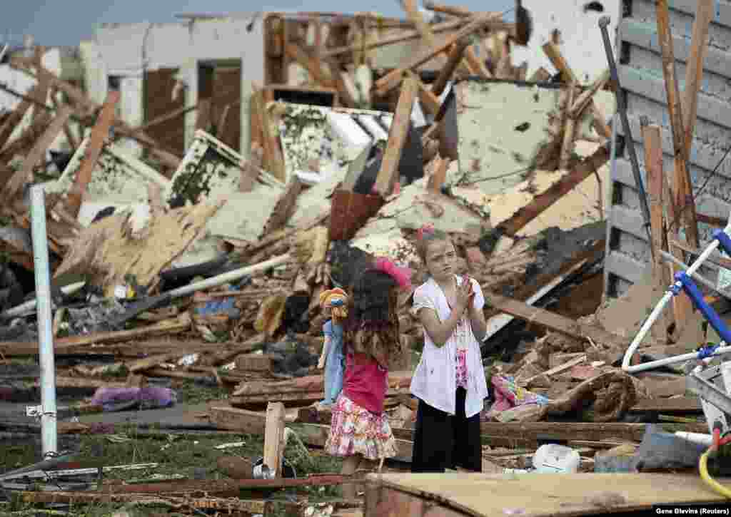 Two girls stand in the rubble of a destroyed neighborhood.
