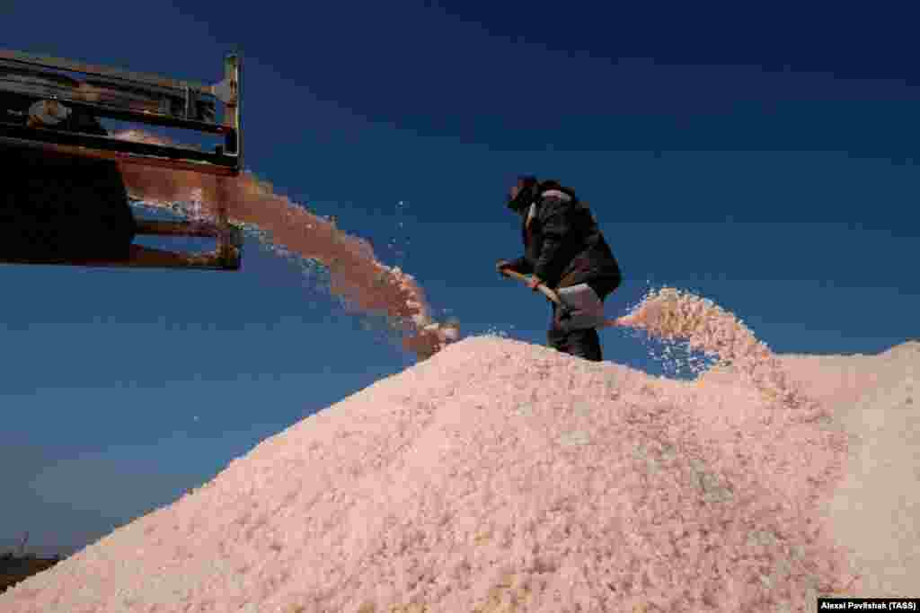 A man shovels salt at the top of a heap. The rare pink salt is exported to European countries and to Japan, where it is prized for its purported value in fighting the effects of radiation.