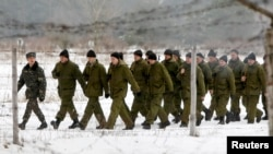 "Newly mobilized Ukrainian soldiers march as they take part in training at the 169th training center of Ukrainian ground forces ""Desna"" in the Chernihiv region on February 13."