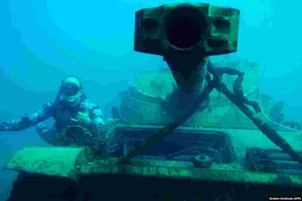 A diver poses for a photograph next to an immersed tank 3 kilometers off the coast of the southern Lebanese port city of Sidon, where environmental activists dropped old battle tanks provided by the Lebanese Army into the Mediterranean Sea to create new habitat for marine life. (AFP/Ibrahim Chalhoub)