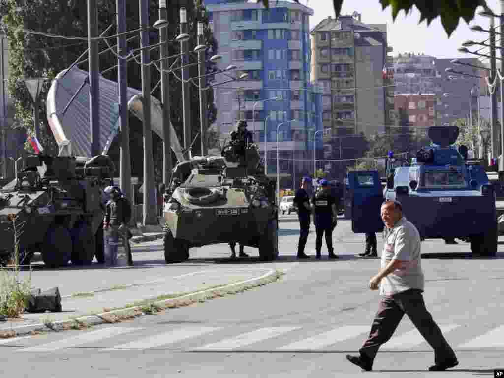 Čovek prolazi ispred vojnika KFOR-a i pripadnika EU policije koji čuvaju glavni most u Mitrovici koji deli grad na severni i južni deo, 28. jul 2011.