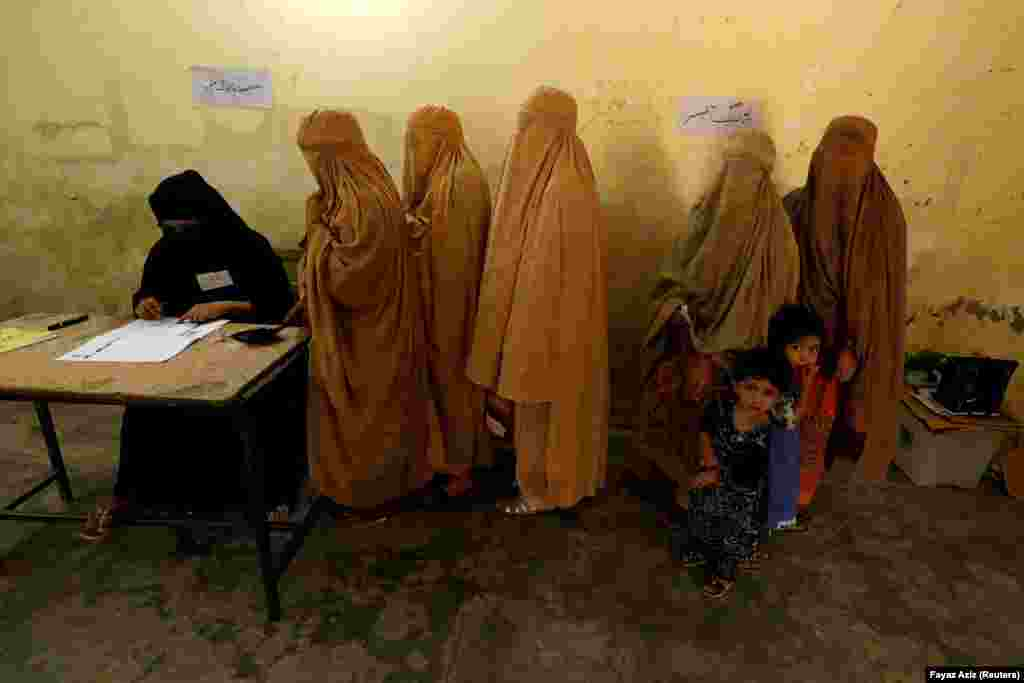 Women, clad in burqas, stand in line to cast their ballots at a polling station during Pakistan's national elections in Peshawar on July 25. (Reuters/Fayaz Aziz)