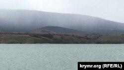 Qarasuvbazar suv anbarı yanında qar bulutlarının örtülen dağlar
