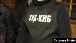 Человек в форме с нашивкой ҰҚК - КНБ (комитет национальной безопасности).