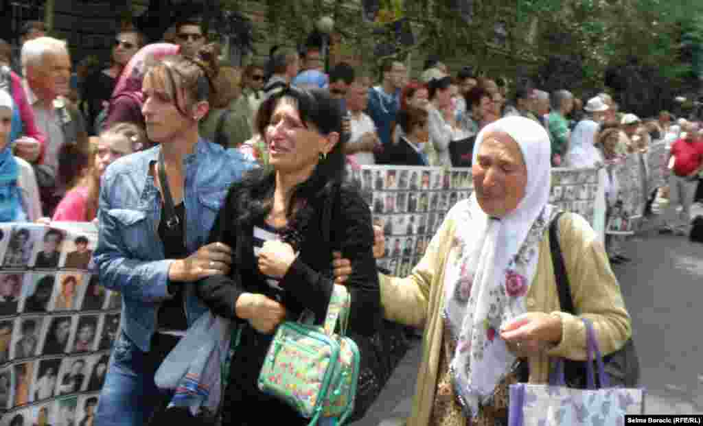 Bosnian women cry while watching a truck, one of three carrying 409 coffins of newly identified victims.