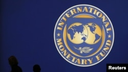 Japan -- Visitors are silhouetted against the logo of the International Monetary Fund at the main venue for the IMF and World Bank annual meeting in Tokyo, 10Oct2012