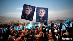 Supporters of Afghan presidential candidate Abdullah Abdullah hold posters of him during an election rally in Parwan Province on March 20.