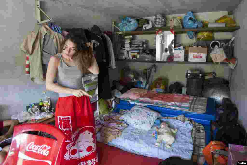 Political activist Natalia Sokol brushes her hair as Gera, the baby of fellow activist Nadezhda Tolokonnikova, lies on a mattress in the car shed that served as the home of the Voina activist group in Moscow in July 2008.
