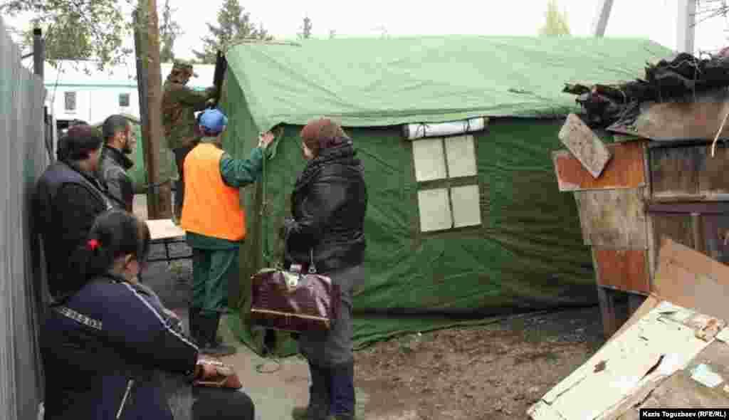 Сотрудники службы спасения устанавливают палатку. Погорельцы наблюдают за процессом.