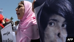 University students and independent civil society activists take part in a demonstration in support of passing the Elimination of Violence Against Women law in front of parliament in Kabul on May 27.