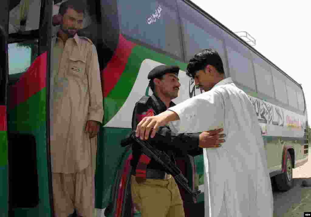 Pakistan -- A Pakistani Policeman inspects the passengers of the first regular Pak-Afghan Bus (Peshawar-Jalalabad Bus) as the bus leaves Peshawar for Jalalabad, 26 May 2006 - PAKISTAN AFGHANISTAN epa00722885 A Pakistani Policeman inspects the passengers of the first regular Pak-Afghan Bus (Peshawar-Jalalabad Bus) as the bus leaves Peshawar for Jalalabad on Friday 26 May 2006. Pakistan and Afghanistan on Friday began the first ever bus service between their main border cities as the two capitals try to calm recent tension over the cross-border infiltration of Islamic militants. EPA