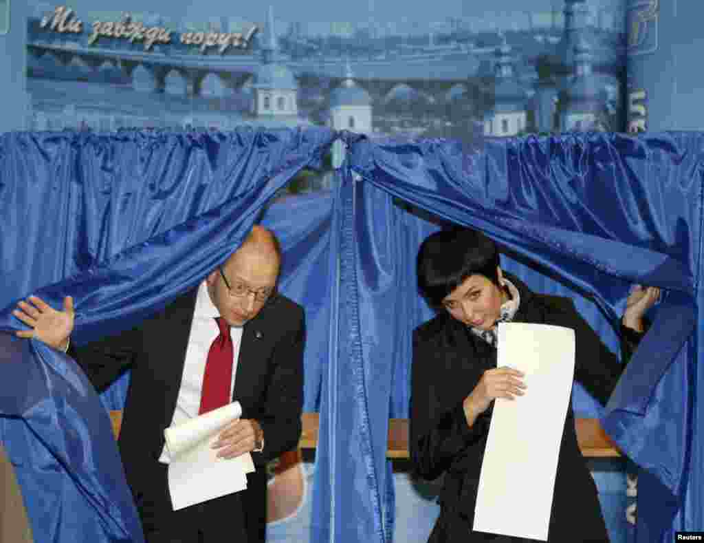 Ukraine - Arseny Yatsenyuk (L), who heads a union of opposition parties, and his wife Theresa leave voting booths at a polling station during the parliamentary elections in Kiev, October 28, 2012.