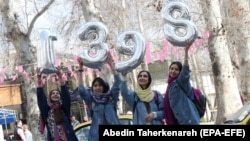 Iranian women hold numbers forming the Persian New Year 1398, Norooz, on New Year eve in Tehran, March 20, 2019