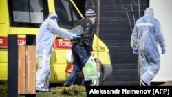 Медики ведут мужчину в госпиталь, где лечат заболевших COVID-19. Москва, 28 апреля 2020 года.