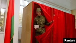 A soldier leaves a voting booth in Minsk to cast his ballot during early voting for Belarus's parliamentary elections.