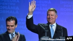 Romanian President Klaus Iohannis (right) with Prime Minister Ludovic Orban by his side waves to supporters after the first-round results are announced.