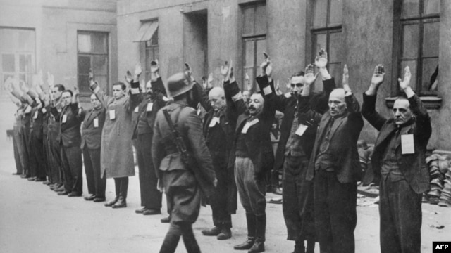 A member of the Nazi SS inspects a group of Jewish workers in the Warsaw ghetto in April 1943.