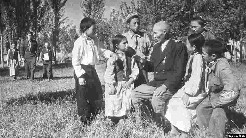 Оқушылармен сөйлесіп отырған ауыл мұғалімі. Қазақ ССР-і, 1950 жылдардың соңы.