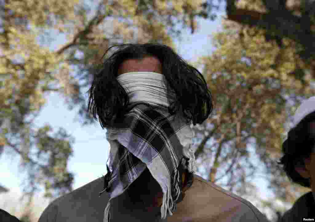 A Taliban militant who was arrested by Afghan police stands with other suspected militants during a presentation to the media in Jalalabad. (Reuters/Parwiz)
