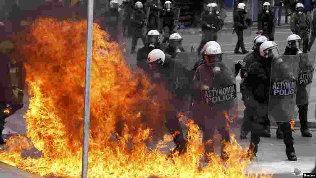 A petrol bomb explodes near Greek riot police during protests against planned austerity reforms in Athens on February 10. (REUTERS/Yiorgos Karahalis)