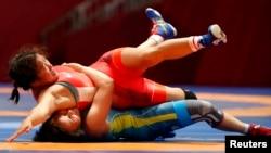 Казахстанская борчиха Жулдыз Эшимова (в синей форме) в схватке с соперницей из Моноголии в полуфинале. Джакарта, 20 августа 2018 года.
